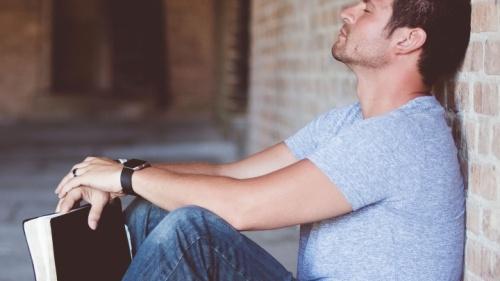 Um homem segurando sua Bíblia de costas a uma parede - com os olhos fechados e orando.