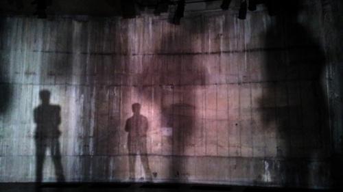 Silhuetas de duas pessoas em uma parede suja.