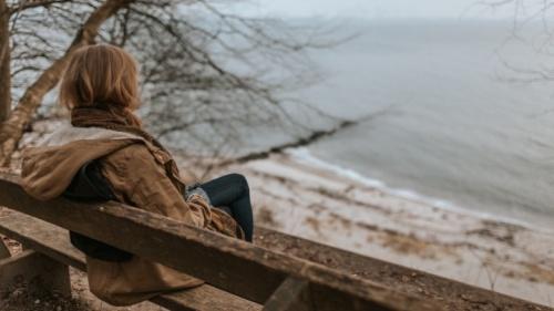 Uma senhora sentada num banco.