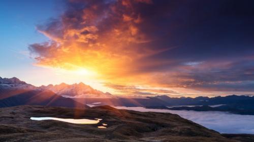 Raios solares sobre uma montanha e um lago.