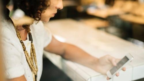 Uma mulher olhando para o seu smartphone.