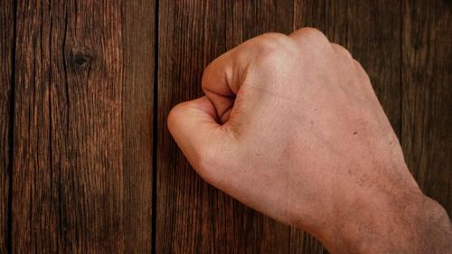 Um punho fechado batendo à porta.