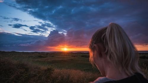 Uma mulher num campo com o pôr do sol à distância.