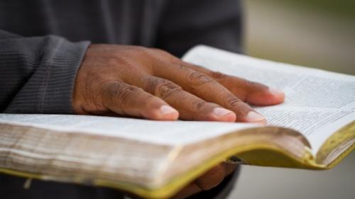 Um homem que segura uma Bíblia aberta.