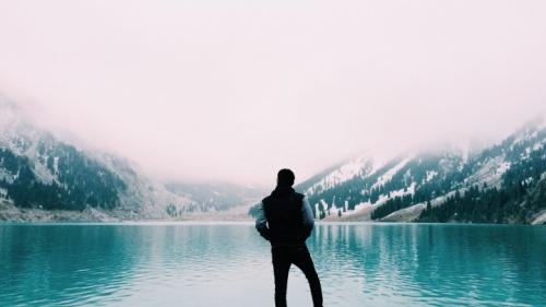 Um homem admirando um lago azul.