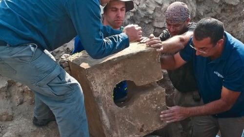 Os escavadores removem uma toalete de pedra que foi usada para contaminar o santuário onde o altar foi encontrado.