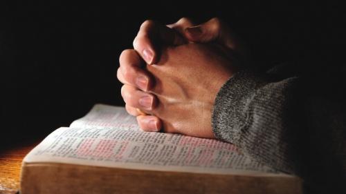Mãos entrelaçadas em cima de uma Bíblia aberta.