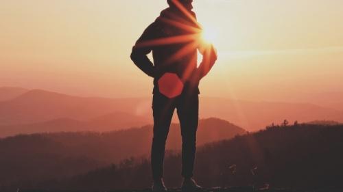 Uma pessoa que está na rocha com o sol atrás deles.