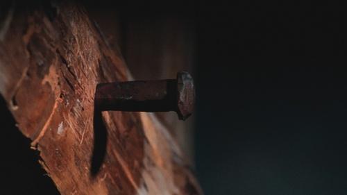 Uma antiga estaca de metal pregada a uma viga de madeira.
