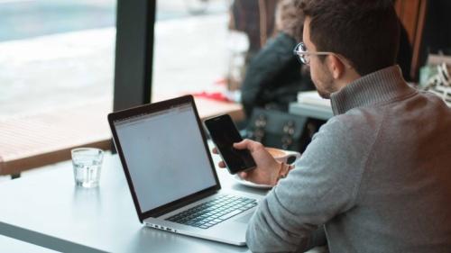 Um homem que usa seu portátil e telemóvel enquanto está num café.
