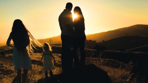 Uma família no campo ao pôr do sol.