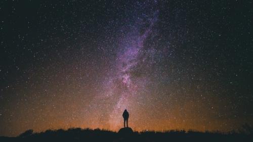 Uma pessoa de noite com as estrelas no fundo.