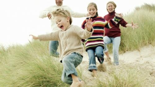 Uma família correndo na praia com grama.