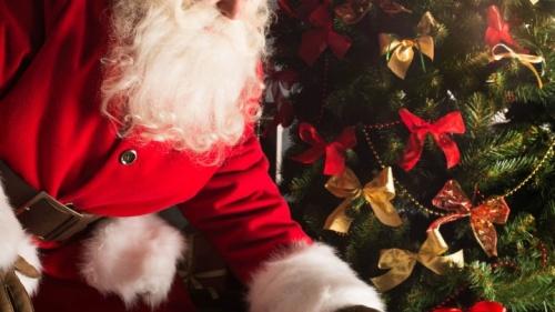Papai Noel colocando presentes de Natal numa árvore.