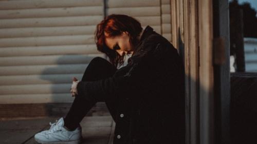 Uma jovem sentada no chão debruçada como se estivesse com dificuldades na vida.