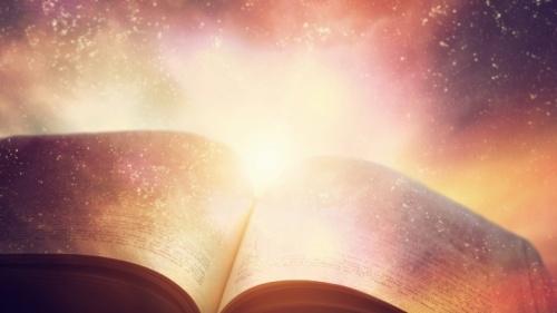 Uma Bíblia aberta com luz ao seu redor.