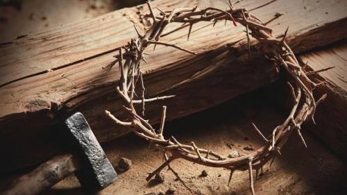 Uma cruz / estaca de madeira com uma coroa de espinhos, martelo e pregos.