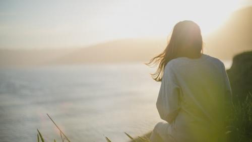 Uma mulher sentada olhando para o pôr do sol.