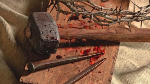 Martelo usado, pregos e espinhos.