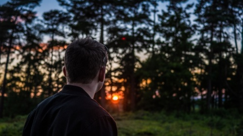 Um homem com o sol atrás das árvores.