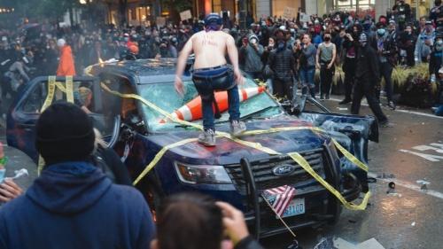 Manifestantes destroem um veículo da polícia em Seattle.