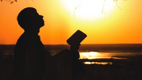 Uma pessoa segurando uma Bíblia e olhando para o céu.
