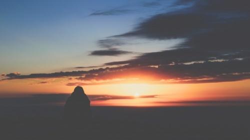Uma pessoa assistindo o pôr do sol.