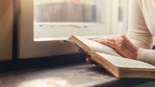 Uma mulher lendo a Bíblia.