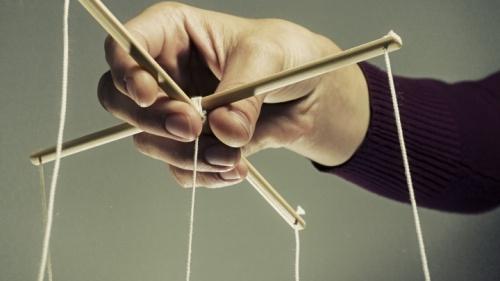 Uma pessoa segurando cordas de uma marionete.