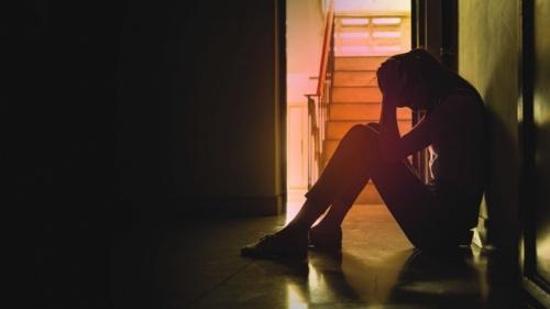 Uma mulher triste sentada no chão num corredor.