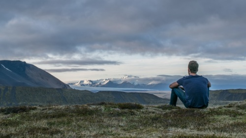Um homem sentado no chão olhando para a paisagem.