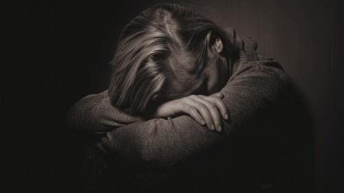 Uma mulher com a sua cabeça em seus braços.