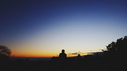 Uma pessoa sentada no topo da colina olhando para a extensão do céu noturno.