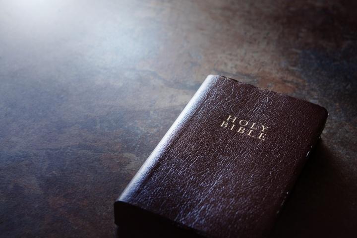 Uma bíblia sobre uma mesa castanha.