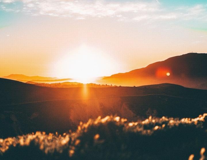 Um pôr-do-sol sobre colinas.