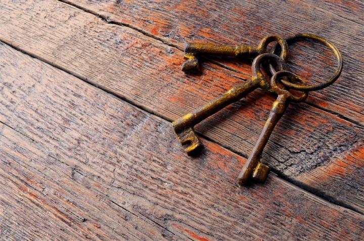Três velhas chaves de esqueleto colocadas sobre uma velha mesa de madeira.