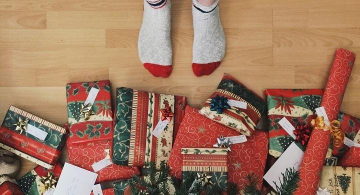 Uma pessoa com meias ao lado de presentes de Natal.
