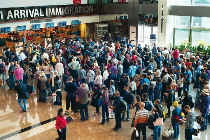 Viajantes em pé na fila do aeroporto para passar pela imigração e alfândega.