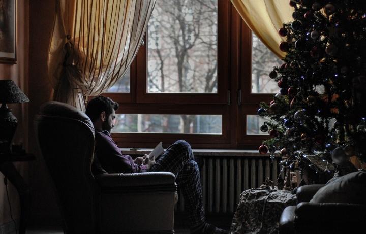 Um homem sentado em uma cadeira em frente a uma árvore de Natal.