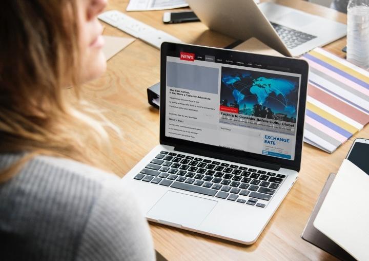 Uma mulher que olha artigos da notícia em um portátil.