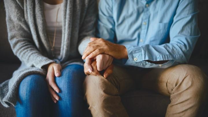 Um marido e esposa sentados de mãos dadas.