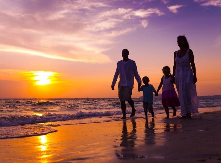 Uma família de quatro pessoas passeando na praia ao pôr do sol.