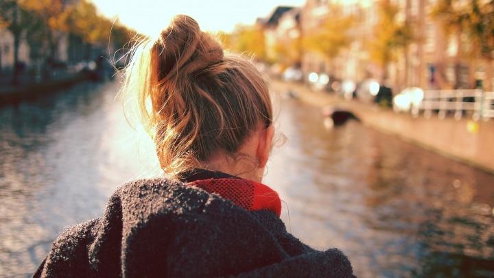 Uma mulher olhando para a água corrente perto duma ponte.