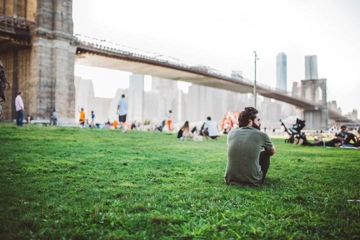 Pessoas sentadas num parque ao lado duma grande ponte.