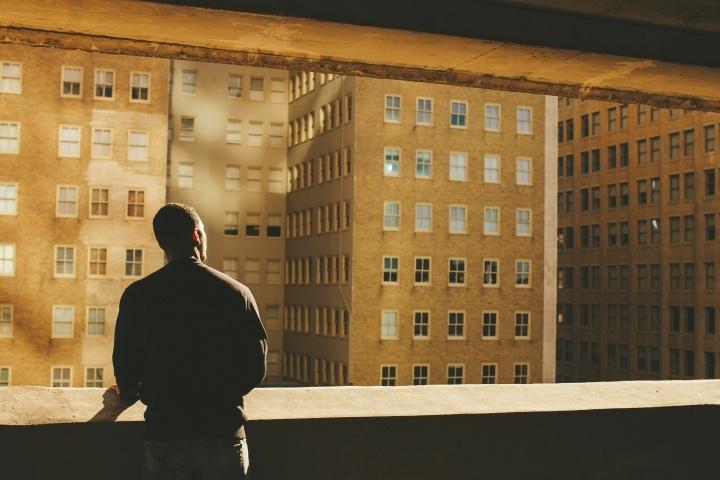 Uma pessoa olhando por cima duma parede para edifícios numa cidade.