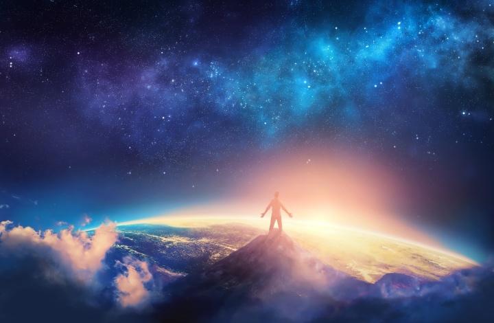 Uma pessoa levantando suas mãos no céu noturno.