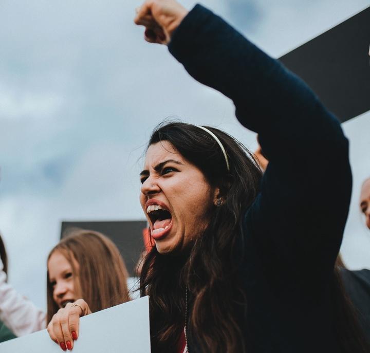 Uma mulher furiosa gritando com o punho no ar.