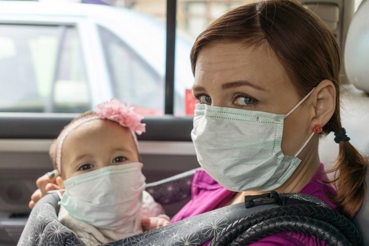Uma mulher e uma criança pequena usando máscaras, sentados num carro.