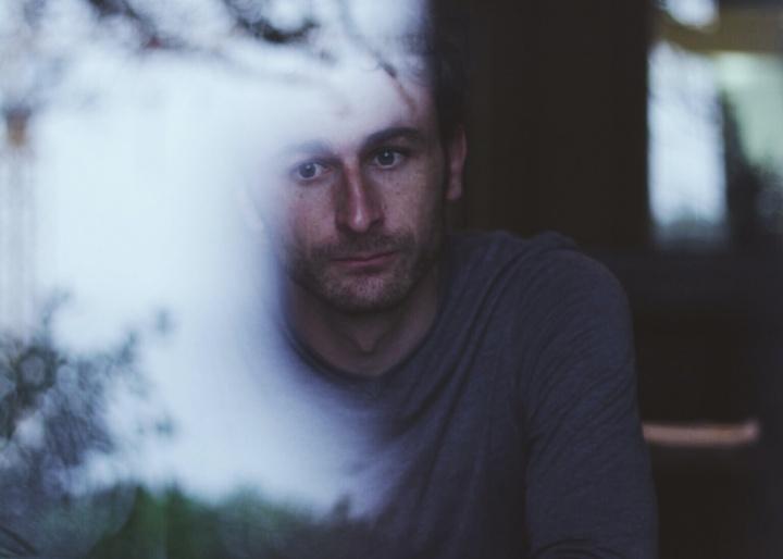 Olhando a um homem sentado à janela.