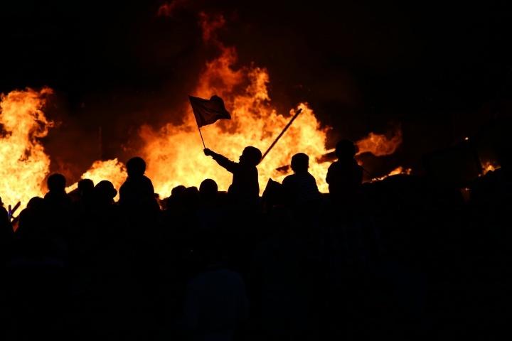 Pessoas em um tumulto queimando itens.